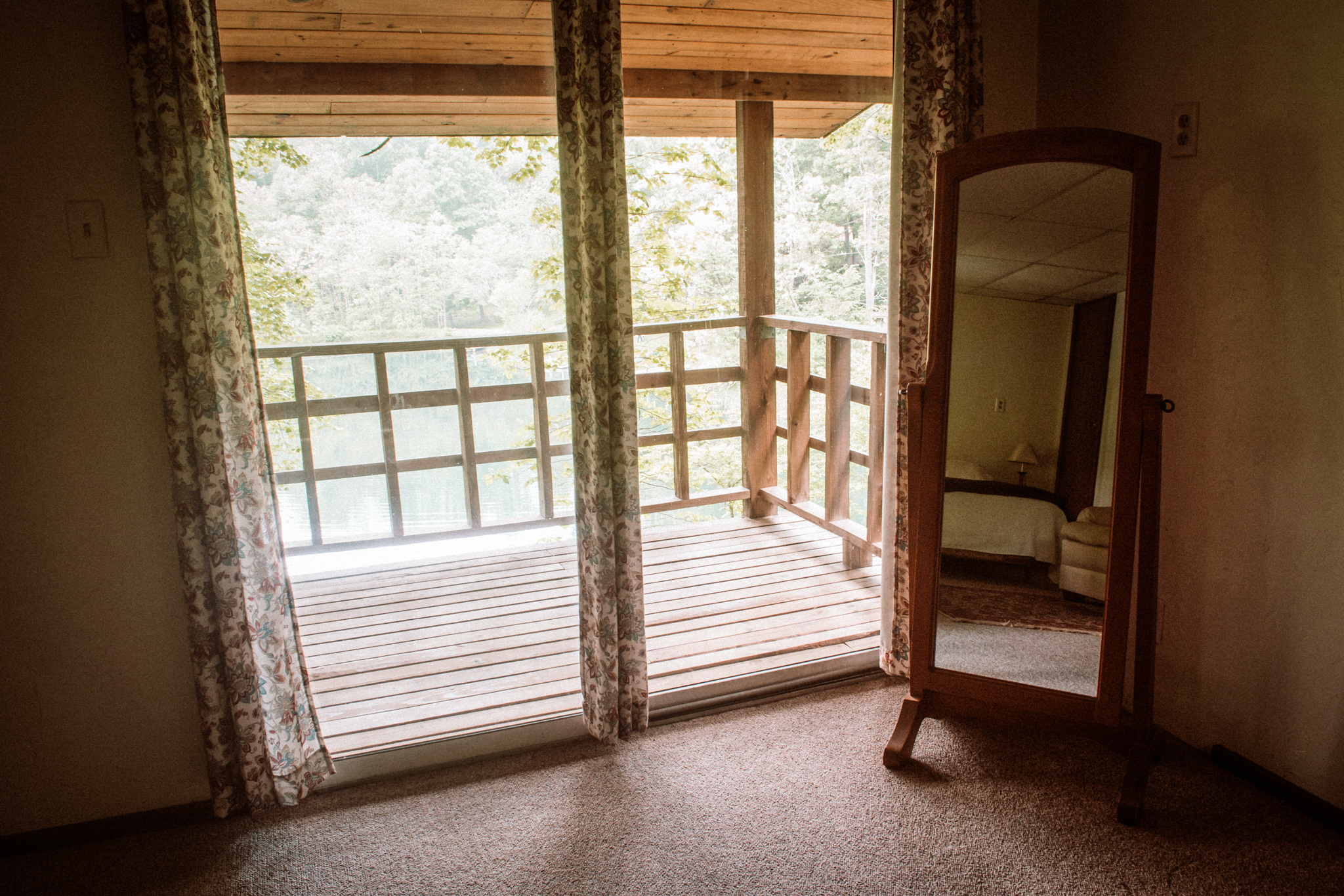 Upstairs King Bedroom in Cedar House - View of Bedroom in Mirror with view of porch. Deck overlooks lake.