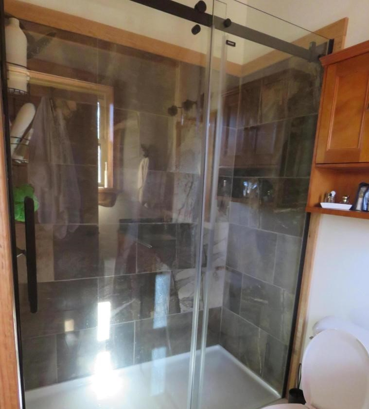 Bathroom - Both full baths offer tile surrounds and glass doors.