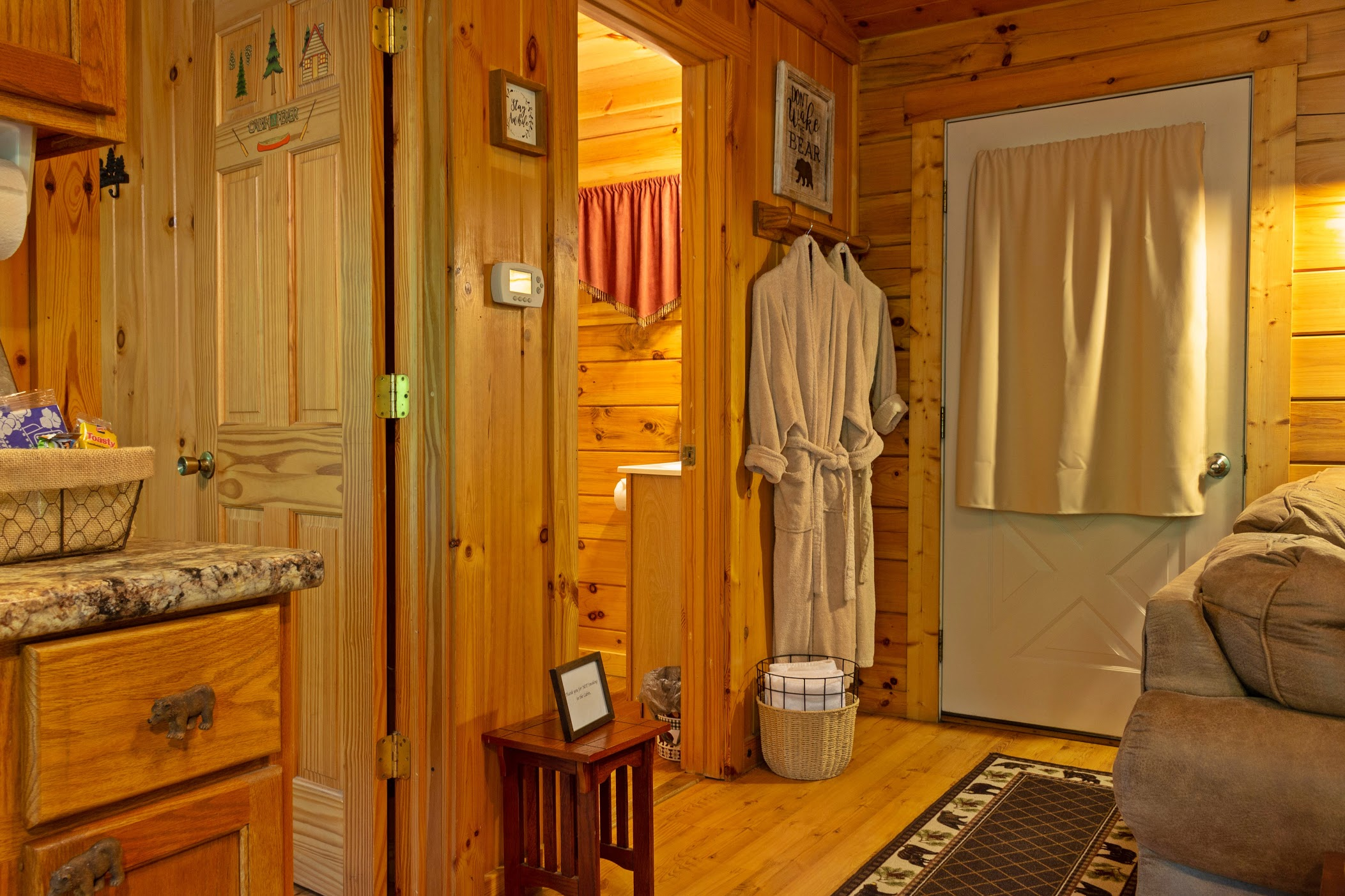 Photo 1407_8960.jpg - This view from the kitchen first shows the bedroom door, then the bathroom door and next to the back door are towels and robes for your use to the hottub.